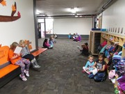 picture of second grade students reading to preschool students